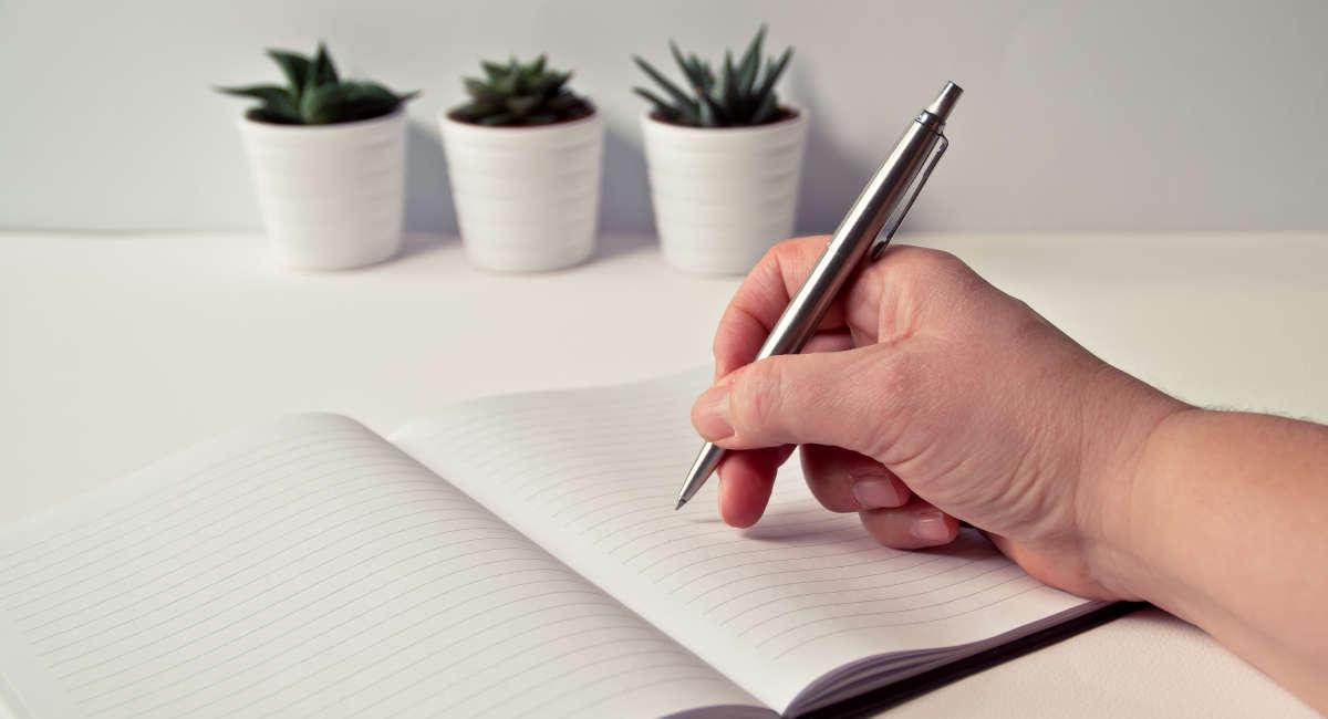 Mano con boligrafo sobre un cuaderno en blanco que representa la confección de la estrategia de employee engagement en la empresa