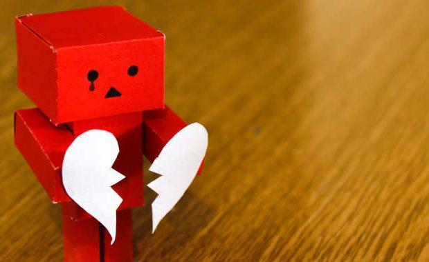 Robot de cartón rojo con un corazón roto porque no está en aceptación con la situación