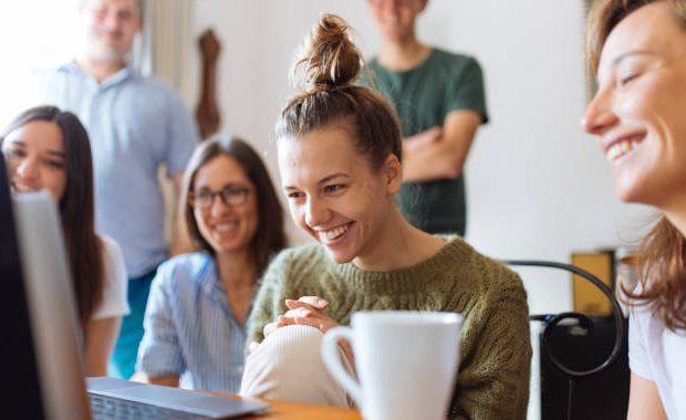 mujer sonriente trabajando en equipo porque disfruta su trabajo